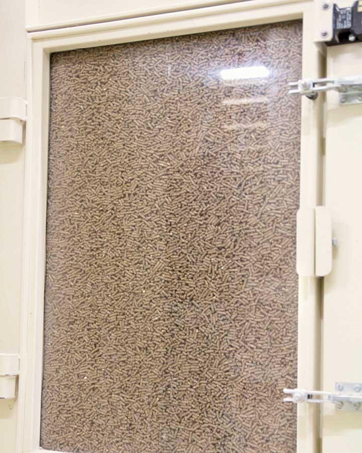 Durch das Sichtfenster des Kühlers sieht man die Pellets ganz langsam von oben nach unten sacken. Dabei werden sie mit Luft schonend gekühlt und verlieren dabei Feuchtigkeit.